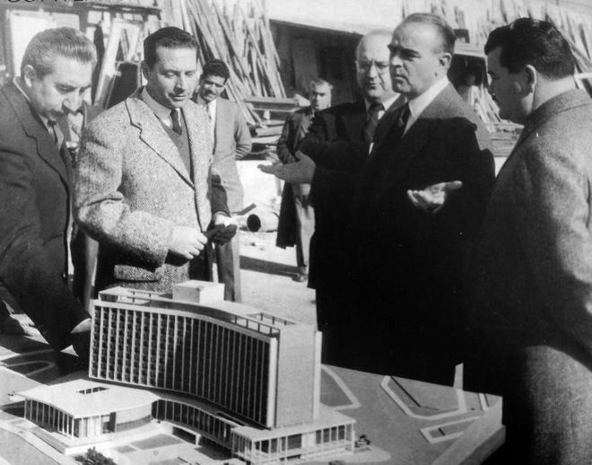 Ο τότε πρωθυπουργός Κωνσταντίνος Καραμανλής εξετάζει τη μακέτα του ξενοδοχείου. Μαζί του είναι ο μετέπειτα Πρόεδρος της Δημοκρατίας Κωνσταντίνος Τσάτσος, ο τότε Υπουργός Εμμανουήλ Κεφαλογιάννης και οι αρχιτέκτονες Αντώνης Γεωργιάδης και Σπύρος Στάικος- 1959