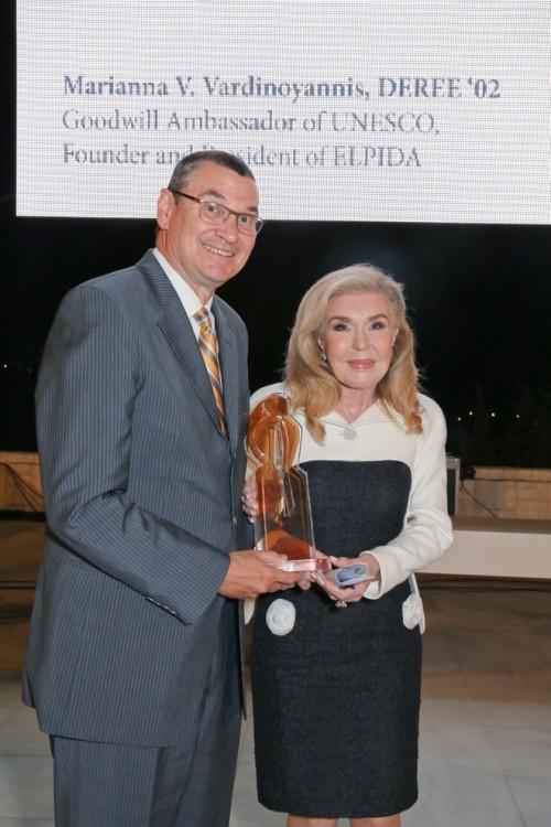 """Ο Πρόεδρος του Αμερικάνικου Κολλεγίου Ελλάδος, Dr. David G. Horner τιμάει την Μαριάννα Β. Βαρδινογιάννη με το Βραβείο """"Maria West Lifetime Achievement"""". Η κ. Βαρδινογιάννη αφηγήθηκε πως εκπλήρωσε ένα όνειρο ζωής όταν απέκτησε το ΒΑ της στην Ιστορία της Τέχνης, από το Deree το 2002"""