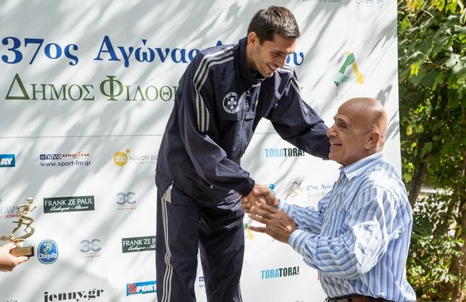 Ο Ολυμπιονίκης Πέτρος Γαλακτόπουλος απονέμει τον δρομέα Μιχάλη Καλομοίρη για την 1η θέση που κατέλαβε στα 10 χιλιόμετρα