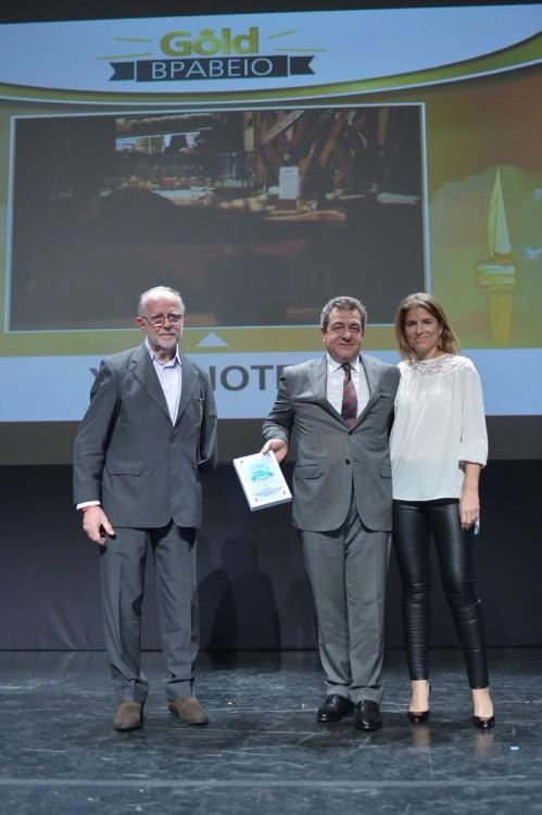 Ο Παύλος Ζορμπάς και η Στεφανία Φλέγγα παραλαμβάνουν το Χρυσό Βραβείο στην κατηγορία «Σχεδιασμός & Λειτουργικότητες Δωματίων» για τα YES!HOTELS από τον Γιάννη Τσεκλένη, μέλος της κριτικής επιτροπής