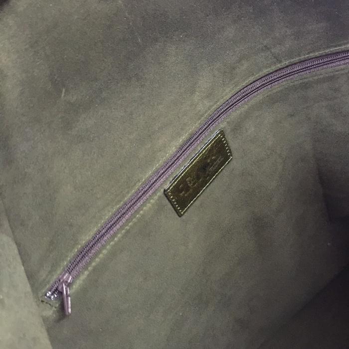 Ένα μοβ φερμουάρ για το εσωτερικό πορτοφόλι, και το όνομα του Fay's Control σε μία δερμάτινη ετικέτα...
