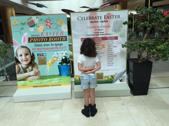 "H ώρα του παιδιού...Η Ελμίνα ενημερώνεται για το παιδικό πρόγραμμα του Golden Hall. Και προσπαθεί να αποφασίσει σε ποια δραστηριότητα θα πρώτο πάμε: Στο Kids Easter Digital Corner, στο Lego Easter Event, στο Πασχαλινό Εργαστήρι Χειροτεχνίας να φτιάξουμε Πασχαλινά προβατάκια, να φωτογραφηθούμε με τον Easter Bunny, στο Gymboree Play & Music, στο Tattoo & Face Painting, στο Funky Easter Puppets, στο Easter Golf, στο Sticks Puzzle, ή στο Easter Digital Photo Booth? ""Σε όλα!"" η απάντηση της Ελμίνας..."