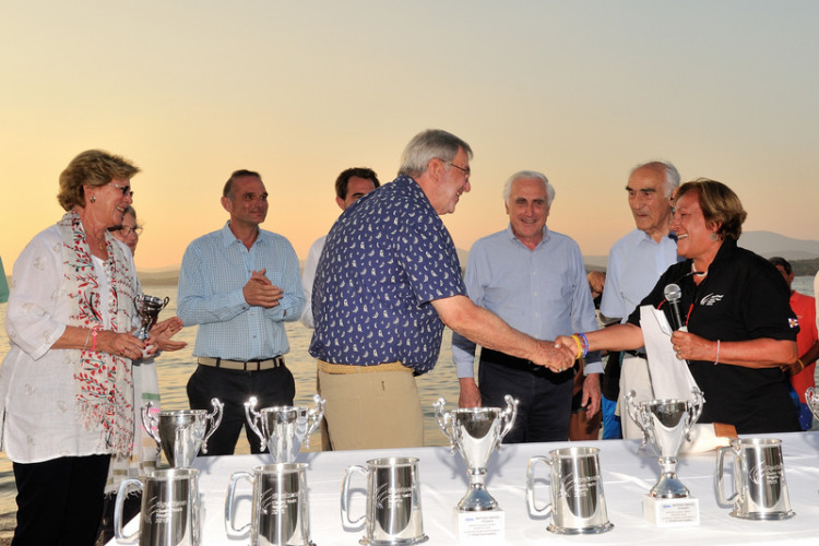 O Βασιλιάς και η Βασίλισσα μαζί με τον Πρόεδρο της Διεθνούς Ομοσπονδίας Ιστιοπλοίας παραλαμβάνουν το έπαθλο για το πρώτο τερματίσαν σκάφος από την Λίζα Σταθάτου, μέλος του ΔΣ ΝΟΕ
