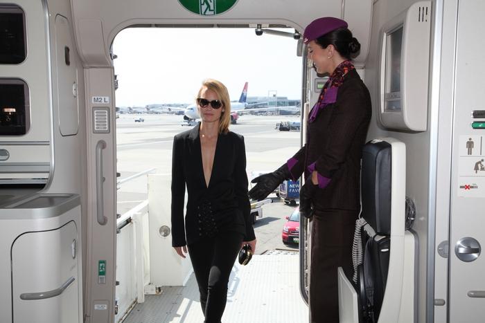 """Το supermodel Amber Valletta καλωσορίζεται από μέλος του πληρώματος της καμπίνας του αεροσκάφους της Etihad Airways που φέρει τα ειδικά διακριτικά """"NYFW: The Shows"""""""
