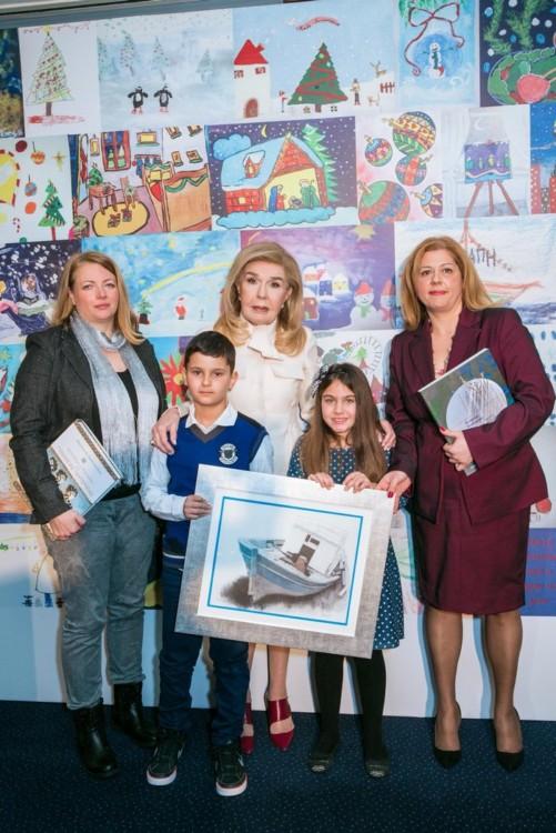 5. Η Μαριάννα Β. Βαρδινογιάννη ανάμεσα στην Αθανασία Γιαξίδου (αριστερά), δασκάλα της Χαράς Μπαζιώτη, και την Αικατερίνη Λέγγου (δεξιά), ο μαθητής Θανάσης Σωτηρόπουλος, νικητής του περσινού διαγωνισμού παιδικής ζωγραφικής και η νικήτρια του φετινού, μαθήτρια Χαρά Μπαζιώτη.