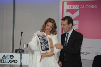 Η Υφυπουργός Πολιτισμού και Αθλητισμού κα. Άντζελα Γκερέκου παραλαμβάνει το επετειακό χαρακτικό του Ξενή Σαχίνη για την Art Thessaloniki από τον Πρόεδρο της ΔΕΘ-Helexpo, κ. Τάσο Τζήκα