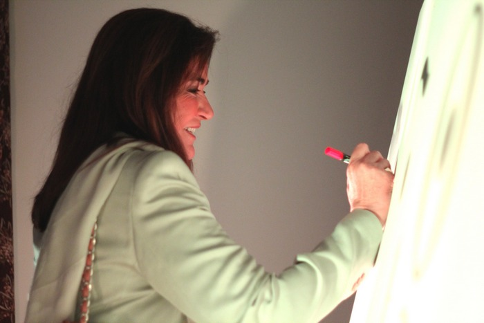 Η Ντόρα Μπακογιάννη αφήνει τις ευχἐς της στον αναμνηστικό πίνακα του Qrator.