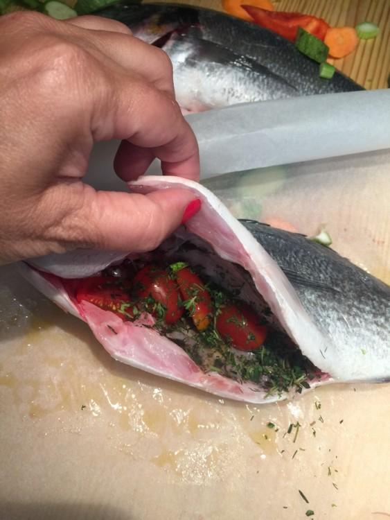 Γεμίζω την κοιλιά του ψαριού με ντοματίνια και ψιλοκομμένο άνιθο και δυόσμο...