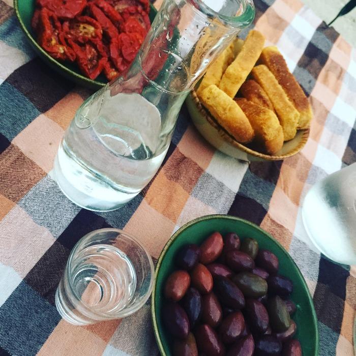 Στο τραπέζι μας τώρα έχουμε τσίπουρο από την Αντίπαρο, Μαριναρισμένες ελιές, Λιαστή ντομάτα από το μποστάνι και Παξιμάδι ελαιόλαδου...