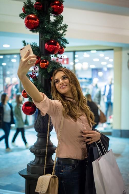 Η Ελένη Τσολάκη βγάζει μία selfie φωτογραφία στο γιορτινό περιβάλλον του εκπτωτικού χωριού McArthurGlen